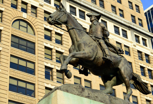 Statue of Caesar Rodney on horseback with state capitol building in background